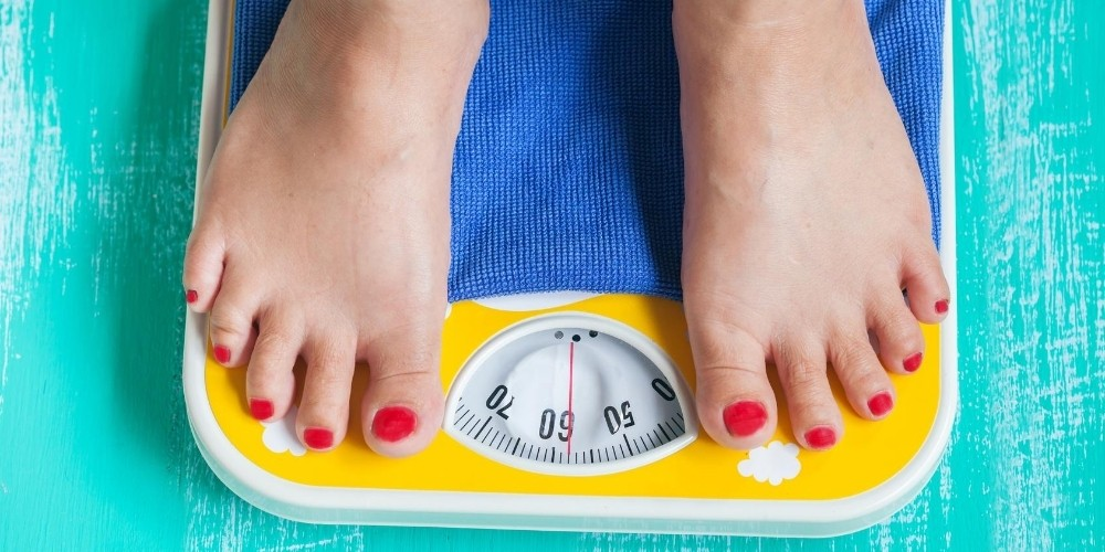 two feet on weight loss scale for denver's omnia health